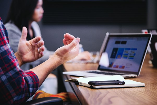 Hands gesturing in front of meeting around table in front of laptop computer