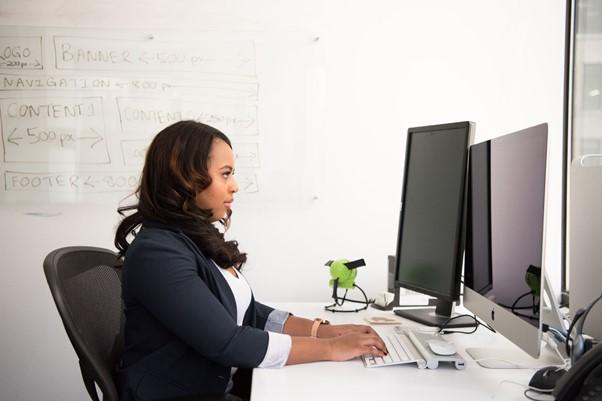 Female web developer sits at desk facing multiple screens